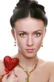 Muchacha joven de la belleza que lleva a cabo el corazón rojo Imagenes de archivo