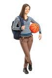 Muchacha joven de la escuela que lleva a cabo un baloncesto Imágenes de archivo libres de regalías