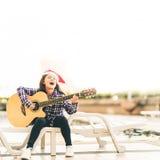 Muchacha joven de la raza mixta que toca la guitarra, cantando y sonriendo alegre por la piscina, con el sombrero de santa de la  Imágenes de archivo libres de regalías