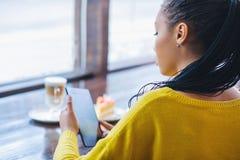Muchacha joven de la raza mixta que usa la tableta digital Imagenes de archivo