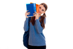 Muchacha joven de los estudiantes de Cutie con la mochila y carpetas para los cuadernos en sus manos que miran la cámara y la son Fotografía de archivo libre de regalías