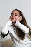 Muchacha joven del adolescente con el teléfono elegante y el auricular que lleva Foto de archivo libre de regalías