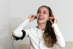 Muchacha joven del adolescente con el teléfono elegante y el auricular que lleva Imágenes de archivo libres de regalías
