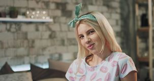 Muchacha joven del adolescente del pelo rubio con las caras atractivas delante de la cámara que come un chicle, mismo sensualidad metrajes