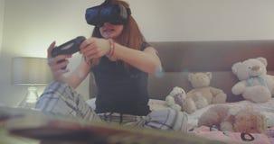 Muchacha joven del adolescente del primer de los detalles que juega en un PSP y que usa los vidrios de una realidad virtual en su almacen de metraje de vídeo
