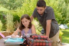 Muchacha joven del adolescente que hace su preparación con su hermano Imagen de archivo libre de regalías