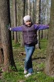 Muchacha joven del adolescente que se coloca entre el tronco dos en un parque Fotografía de archivo