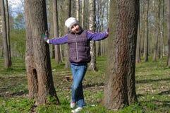 Muchacha joven del adolescente que se coloca entre el tronco dos en un parque Foto de archivo libre de regalías