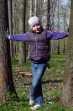 Muchacha joven del adolescente que se coloca entre el tronco dos en un parque Imagen de archivo libre de regalías