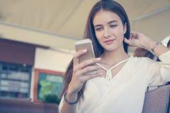 Muchacha joven del adolescente que se sienta en café y que usa el teléfono elegante Foto de archivo