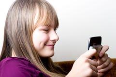 Muchacha joven del adolescente que sostiene el teléfono móvil texting Foto de archivo libre de regalías