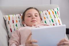 Muchacha joven del adolescente que usa la tableta que se sienta en el sofá Fotografía de archivo libre de regalías