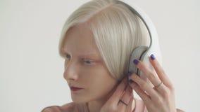 Muchacha joven del albino en los auriculares blancos que escucha la música Bastidor del albino de la muchacha en un estudio de la almacen de metraje de vídeo