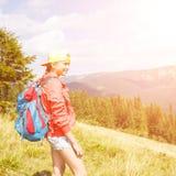 Muchacha joven del backpacker que disfruta de la visión en montañas Fotos de archivo