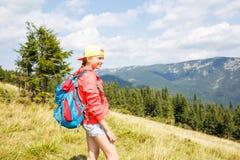 Muchacha joven del backpacker que disfruta de la visión en montañas Imágenes de archivo libres de regalías