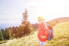 Muchacha joven del backpacker que disfruta de la visión en montañas Foto de archivo