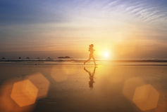 Muchacha joven del basculador que corre a través de la resaca en la puesta del sol asombrosa imagenes de archivo