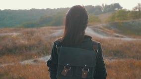 Muchacha joven del caminante con una mochila en las montañas superiores en la puesta del sol Forma de vida, concepto del viaje metrajes