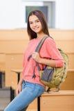 Muchacha joven del estudiante al lado del escritorio Imagenes de archivo