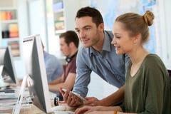 Muchacha joven del estudiante con el profesor que trabaja en un ordenador Fotografía de archivo