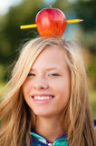 Muchacha joven del estudiante con la manzana en su cabeza Foto de archivo