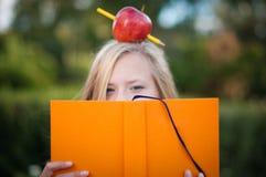 Muchacha joven del estudiante con la manzana en su cabeza Fotografía de archivo