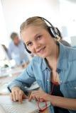 Muchacha joven del estudiante con los auriculares y el ordenador portátil Fotos de archivo libres de regalías