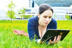 Muchacha joven del estudiante de la belleza con la tableta en la naturaleza Imagen de archivo
