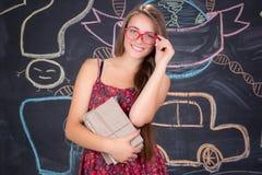 Muchacha joven del estudiante en vidrios rojos con el paquete de libros Fotografía de archivo