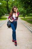 Muchacha joven del estudiante que camina abajo de la calle con una mochila en el parque Fotografía de archivo