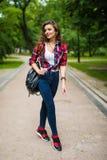 Muchacha joven del estudiante que camina abajo de la calle con una mochila en el parque Foto de archivo libre de regalías