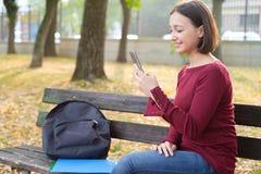 Muchacha joven del estudiante que espera y que sostiene el teléfono móvil en la ciudad Imágenes de archivo libres de regalías