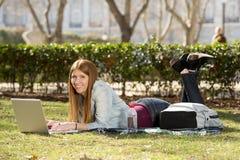 Muchacha joven del estudiante que miente en la hierba del parque con el ordenador que estudia o que practica surf en Internet Fotografía de archivo libre de regalías