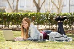 Muchacha joven del estudiante que miente en la hierba del parque con el ordenador que estudia o que practica surf en Internet Foto de archivo