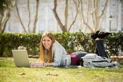Muchacha joven del estudiante que miente en la hierba del parque con el ordenador que estudia o que practica surf en Internet Fotos de archivo