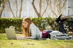 Muchacha joven del estudiante que miente en la hierba del parque con el ordenador que estudia o que practica surf en Internet Imagen de archivo