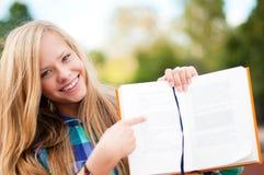 Muchacha joven del estudiante que muestra algo en libro Fotos de archivo libres de regalías