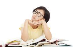 Muchacha joven del estudiante que piensa con el libro en el escritorio Fotos de archivo