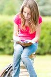 Muchacha joven del estudiante que se sienta en la pila de libros Imágenes de archivo libres de regalías