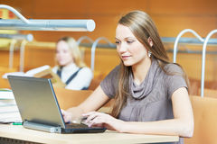 Muchacha joven del estudiante que trabaja con la computadora portátil en biblioteca Foto de archivo libre de regalías