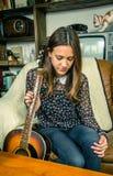 Muchacha joven del inconformista con la guitarra acústica en casa Imágenes de archivo libres de regalías