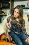 Muchacha joven del inconformista con la guitarra acústica en casa Imagen de archivo libre de regalías