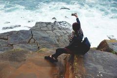 Muchacha joven del inconformista que hace el autorretrato en el teléfono de célula mientras que descansa cerca del mar en día de  Foto de archivo libre de regalías