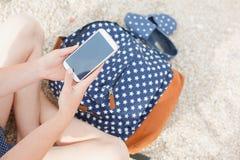 Muchacha joven del inconformista que manda un SMS en un smartphone Imagen de archivo