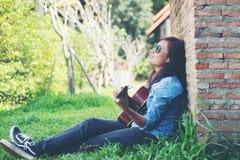 Muchacha joven del inconformista que se sienta tocando una guitarra y cantando Fotos de archivo libres de regalías