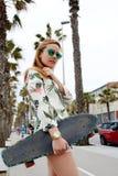 Muchacha joven del inconformista que sostiene el monopatín mientras que ella que se colocaba en el carril alineó con las palmeras Imágenes de archivo libres de regalías
