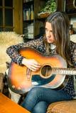 Muchacha joven del inconformista que toca la guitarra acústica en casa Foto de archivo libre de regalías