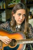 Muchacha joven del inconformista que toca la guitarra acústica en casa Imagenes de archivo