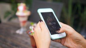 Muchacha joven del inconformista que toma la foto del postre delicioso dulce del helado en la tabla de madera del vintage en rest metrajes