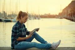 Muchacha joven del inconformista que usa la almohadilla táctil mientras que se sienta contra fondo del puerto marítimo con el esp Fotografía de archivo